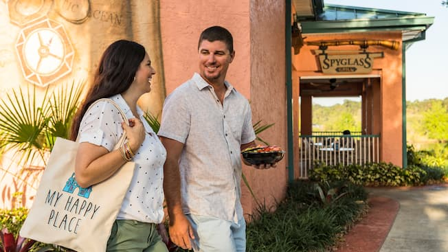 A woman walking next to a man carrying a packaged salad outside a restaurant named Spyglass