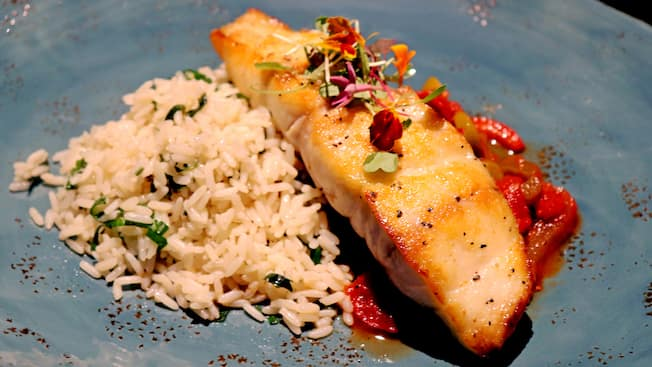 Un pedazo de pescado servido con un acompañante de arroz blanco