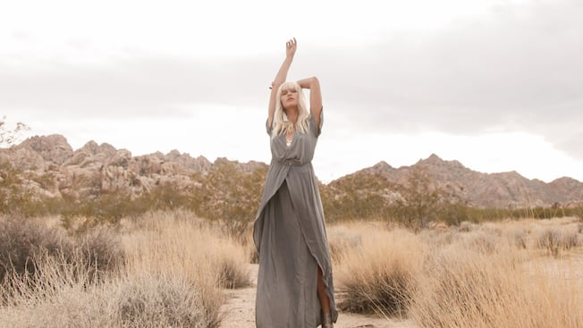 Wearing a flowing dress, a woman in a desert reaches for the sky with her eyes closed