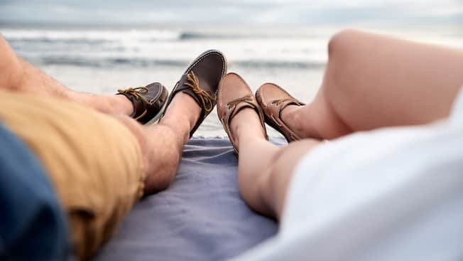 The legs of a man and woman lying on a blanket by the ocean with their shoes touching