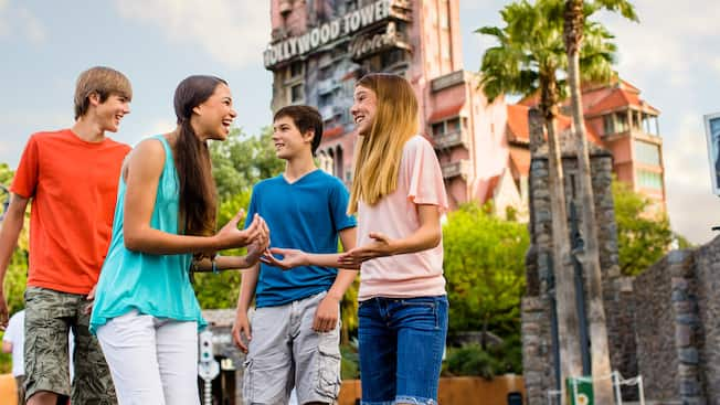 4 excited young Guests talking outside The Twilight Zone Tower of Terror