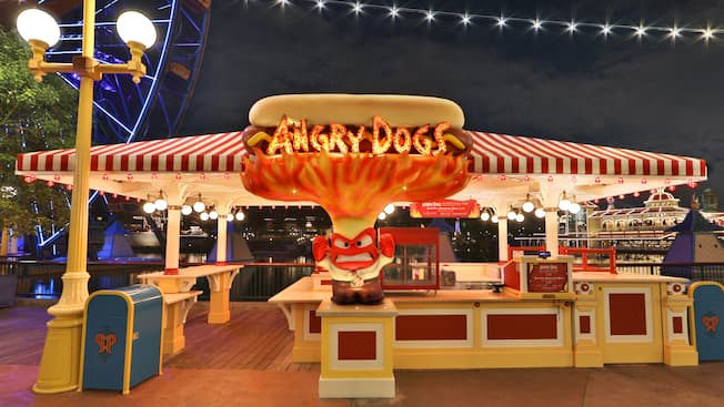 The sign for Angry Dogs features a person clenching his teeth with a flaming hotdog overhead