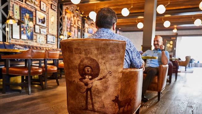Un visitante se sienta en una silla rústica con la ilustración de Miguel de Coco tocando la guitarra