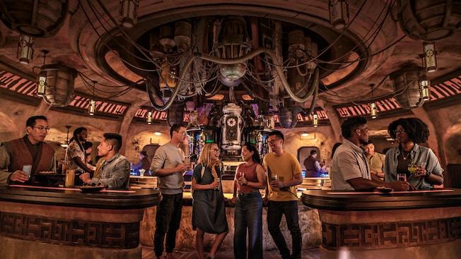 Adultos disfrutan bebidas exóticas dentro de una cantina de Star Wars que tiene cañerías, tubos y máquinas inusuales