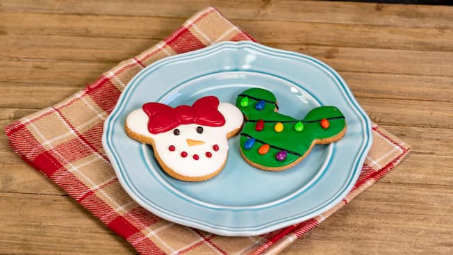 A Mickey ears holiday tree cookie and a Minnie bow snowman face holiday cookie sit on a plate atop a plaid napkin