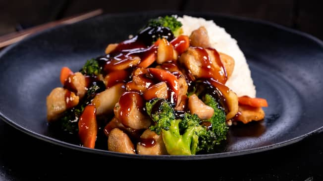 Un plato de pollo teriyaki con vegetales salteados y arroz al vapor sobre un individual de pizarra con palillos chinos a un costado