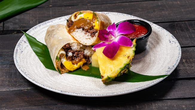 A burrito filled with rice, ground beef, fried egg and gravy on a plate with a cup of sauce, pineapple wedges and an orchid flower