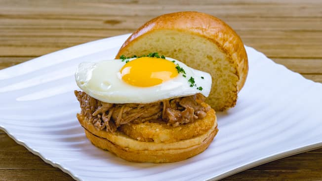 A breakfast sandwich with an egg, shredded pork and hash browns inside
