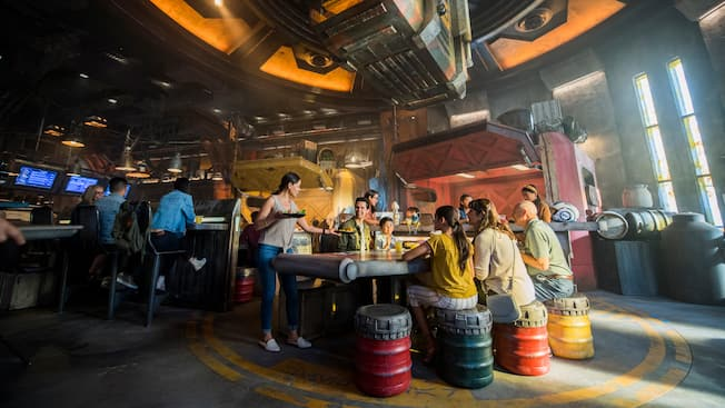 A woman hands food to her family, seated inside a Star Wars cargo building where large containers of food are lowered from the ceiling