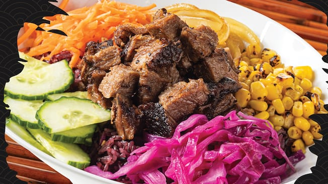 A bowl of meat, cucumbers, corn, onions, carrots and red cabbage from Asian Street Eats