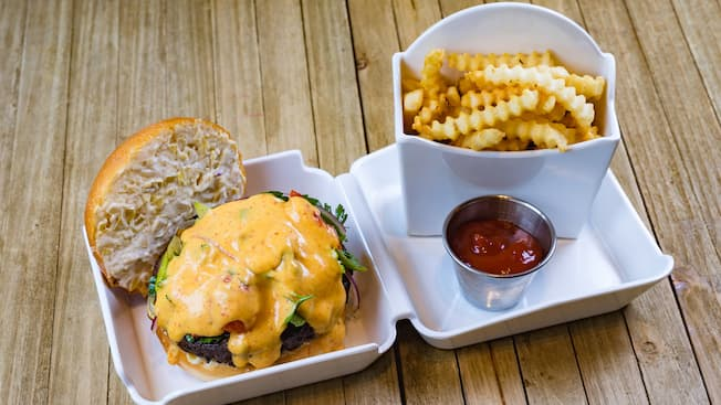 Hamburguesa con ensalada de apio y espárragos asados, salsa holandesa especiada, alioli de queso suizo y alcachofas, servida con papas fritas de corte americano y ketchup.