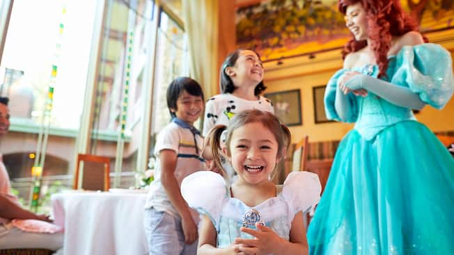 A little girl beams as her brother and sister share a laugh with Princess Ariel in the background