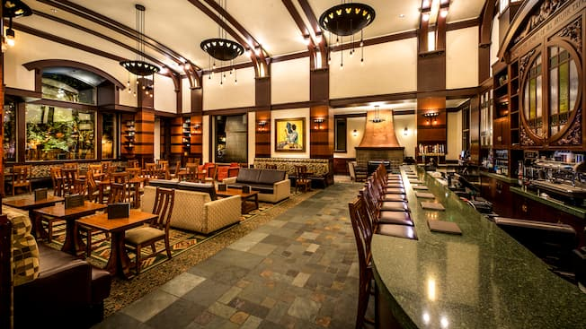 The lodge-style interior of Hearthstone Lounge with dining tables, sofa seating and a bar.