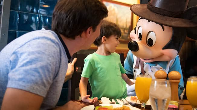 Mickey Mouse, dressed as an explorer, interacts with Guests at Storytellers Cafe