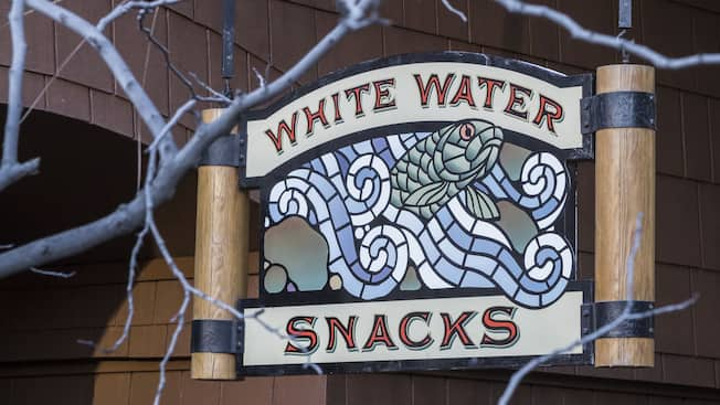 A sign for White Water Snacks, featuring art of a fish emerging from a rough river
