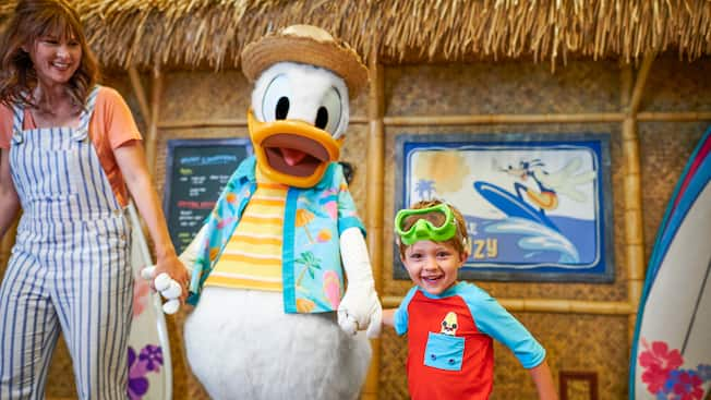Donald Duck walks hand in hand with a woman and her son in front of a restaurant styled like a hut