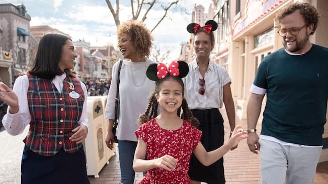 A happy little girl wearing Minnie Ears takes a VIP Tour of the Disneyland Resort with her family