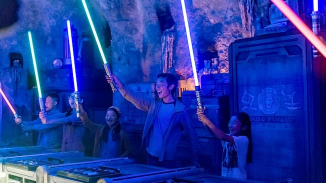 People standing around a circular table hold up newly constructed lightsabers