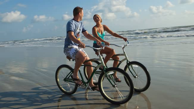 2f94e114aa86 Rentals at Disney's Hilton Head Island Resort. A man and a woman ride  bicycles on the beach's wet sand
