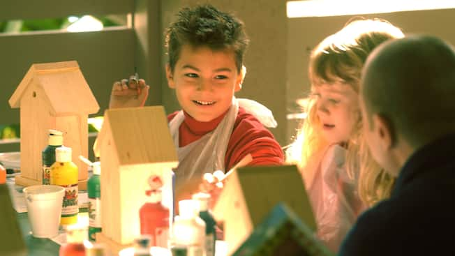 A boy and girl at a crafts table painting birdhouses