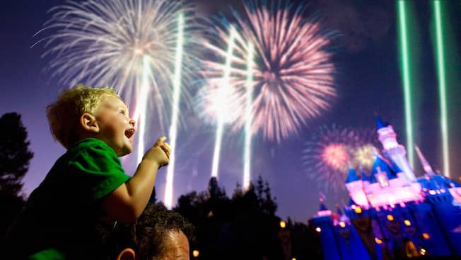 Fireworks in background with little boy smiling