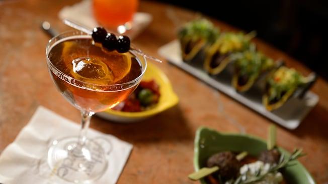 Un palillo con 3 aceitunas descansa sobre el borde de un coctel especial en Carthay Circle Lounge