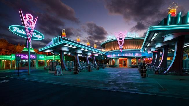 Entrada de Flo's V8 Cafe con el tema de una gasolinera, iluminada por la noche con letreros de neón