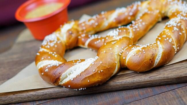 A stack of six freshly baked hot Bavarian pretzels are lightly sprinkled with salt