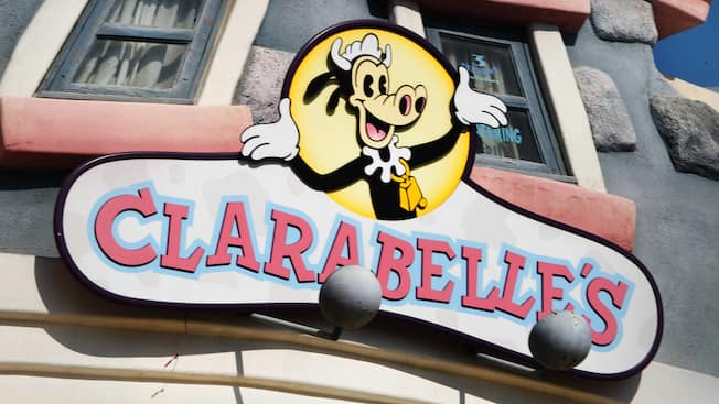 The sign for Clarabelle's snack stand at Disneyland Park features a smiling Clarabelle Cow