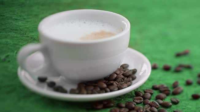A foamy cup of cappuccino from Starbucks plated beside a scattered array of espresso beans