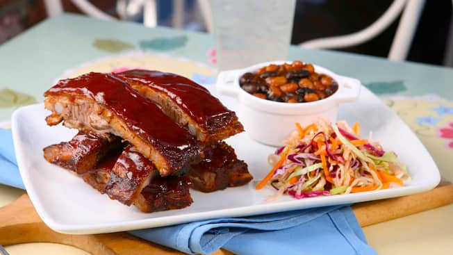 A plate of Spice-rubbed pork spare ribs with baked beans and cole slaw sits on an outdoor café table at the River Belle Restaurant