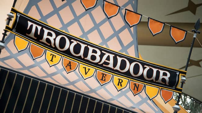 El letrero de Troubadour Tavern, un Restaurante de Fantasyland en Disneyland Park