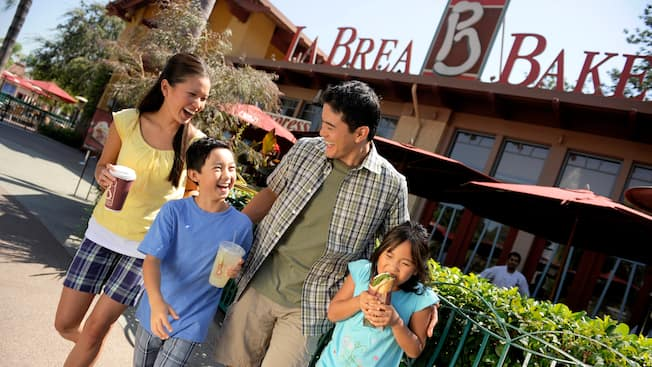 A family of four laughs together while enjoying an assortment of treats from La Brea Bakery Express