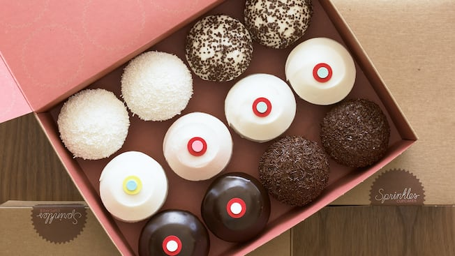 One dozen cupcakes witha variety of decorations and toppings in an open cardboard box