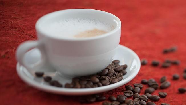 Taza de capuchino con granos de café esparcidos en un platillo y en la mesa