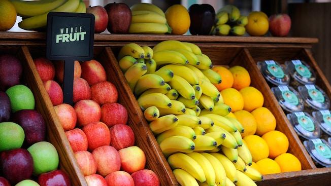 Un puesto de fruta con manzanas, plátanos y naranjas