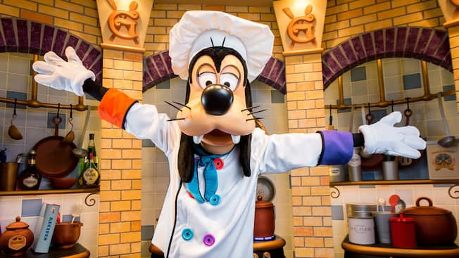 Goofy wearing a chef's ensemble presents his kitchen