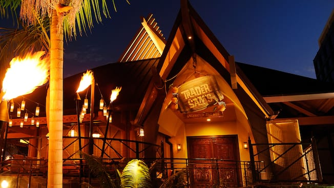 Lit tiki torches at night along the path to Trader Sam's Enchanted Tiki Bar at Disneyland Hotel