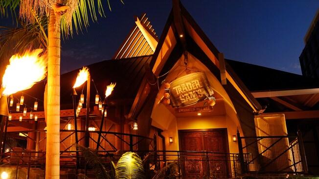 Antorchas tiki encendidas por la noche a lo largo de la ruta hacia Trader Sam's Enchanted Tiki Bar en Disneyland Hotel
