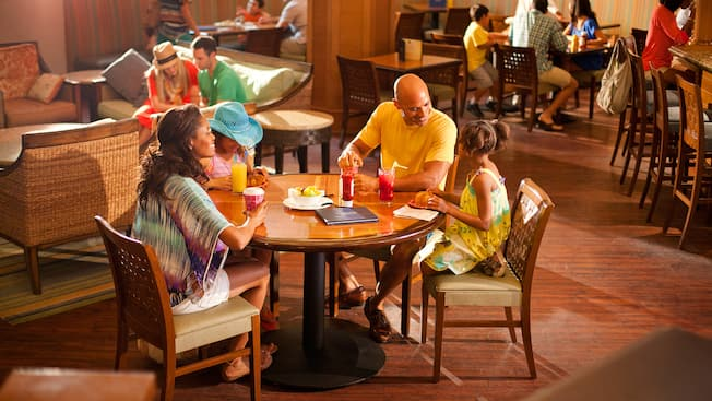 Una familia se relaja con bebidas y un antojito en Surfside Lounge, un restaurante de Paradise Pier Hotel