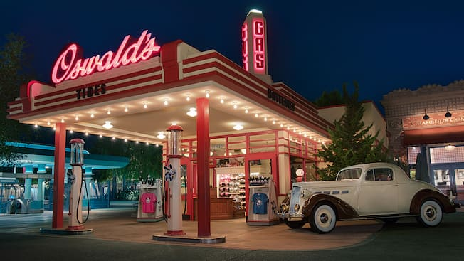 "A shop that resembles a vintage gas station selling Oswald the Lucky Rabbit apparel, toys and Mickey Mouse ear hats with a classic car parked out front and signs that read ""Oswald's, Tires, Batteries and Gas"""