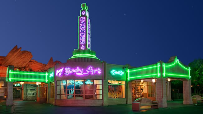 """A shop that resembles a vintage gas station lit up at night by neon lights with signs that read """"Ramones"""" and """"House of Body Art"""" and featuring windows displaying custom-designed automobile hoods"""