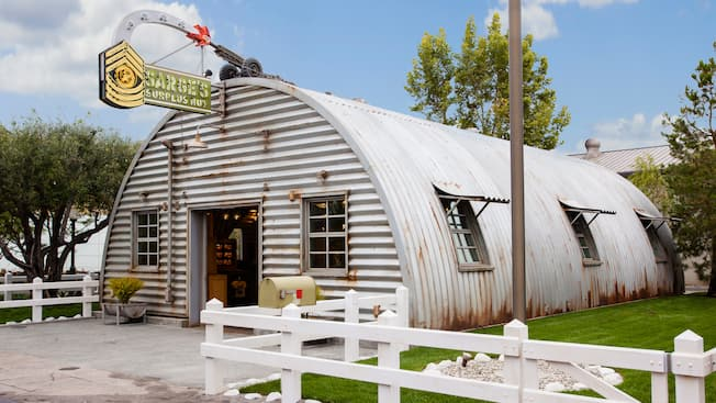 """An slightly rusty corrugated metal Quonset hut with a white picket fence, mailbox, flagpole and a sign resembling a firing artillery gun that reads """"Sarge's Surplus Hut"""""""
