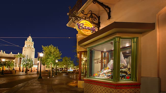 Buena Vista Street glowing at night as sweets are featured in the window display at Trolley Treats