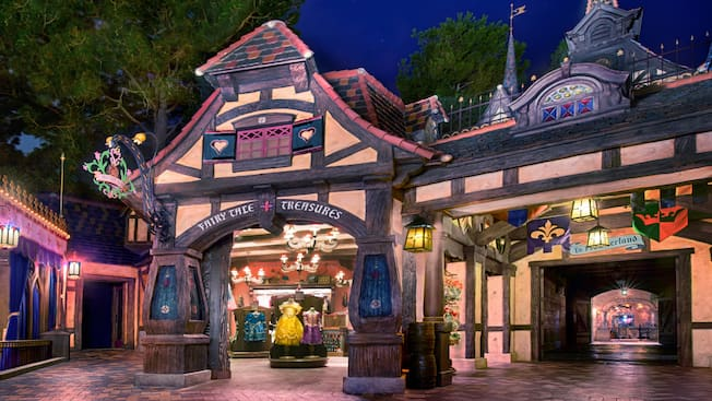 A shop with a half-timber style facade, a sign that reads 'Fairy Tale Treasure' and merchandise that includes ornate princess dresses for children, next to a tunnel with a sign that reads 'To Frontierland'