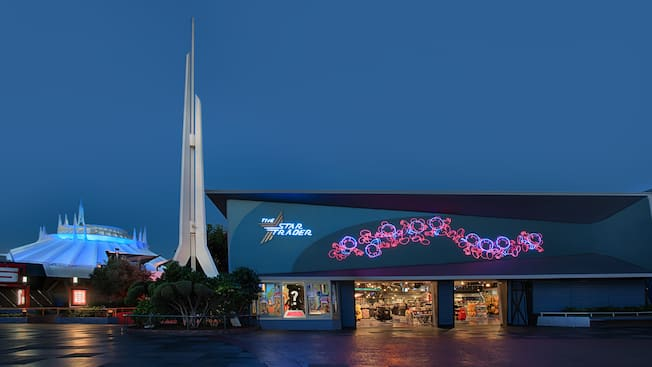 The exterior of Star Trader lights up in evening as spires atop Space Mountain extend toward the sky