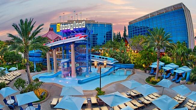 Los rayos del sol iluminan las piscinas, el tobogán de agua, las cabañas frente a la piscina y los camastros entre las palmeras