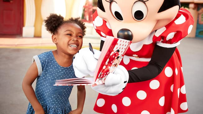 A little girl smiles while Minnie Mouse signs her autograph book