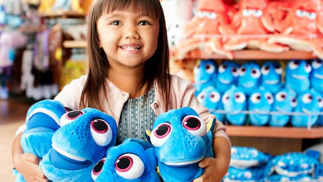 A little girl holds 4 Dory plush toys at a Disney store
