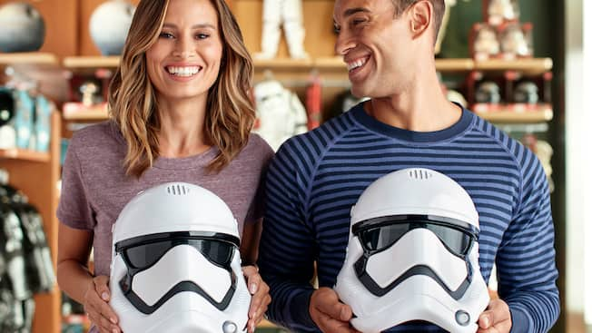 A smiling couple holds a pair of Storm Trooper helmets